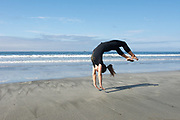 Young woman doing gymnastics on the beach, Washington, USA