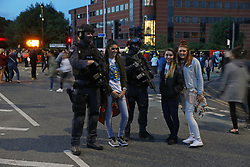 Concert-goers pose for pictures next to armed police as they depart following the One Love Manchester benefit concert for the victims of the Manchester Arena terror attack at Emirates Old Trafford, Greater Manchester.