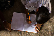Hemant Jat, 6, finishes his homework at home in Maheshwar, Khargone, Madhya Pradesh, India on 13 November 2014. Hemant, the son of a Fairtrade cotton farmer, wants to be a police man when he grows up and gets a 5% discount of school fees at the Vasudha school. His father Nandaram would be happy if Hemant took over the farm but if he does well in school, he could look for other careers. Photo by Suzanne Lee for Fairtrade