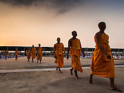 """14 FEBRUARY 2014 - KHLONG LUANG, PATHUM THANI, THAILAND:  Monks file into the main prayer area at Wat Phra Dhammakaya for Makha Bucha Day. The aims of Makha Bucha Day are: not to commit any kind of sins, do only good and purify one's mind. It is a public holiday in Cambodia, Laos, Myanmar and Thailand. Many people go to the temple to perform merit-making activities on Makha Bucha Day. The day marks four important events in Buddhism, which happened nine months after the Enlightenment of the Buddha in northern India; 1,250 disciples came to see the Buddha that evening without being summoned, all of them were Arhantas, Enlightened Ones, and all were ordained by the Buddha himself. The Buddha gave those Arhantas the principles of Buddhism, called """"The ovadhapatimokha"""". Those principles are:  1) To cease from all evil, 2) To do what is good, 3) To cleanse one's mind. The Buddha delivered an important sermon on that day which laid down the principles of the Buddhist teachings. In Thailand, this teaching has been dubbed the """"Heart of Buddhism."""" Wat Phra Dhammakaya is the center of the Dhammakaya Movement, a Buddhist sect founded in the 1970s and led by Phra Dhammachayo.    PHOTO BY JACK KURTZ"""