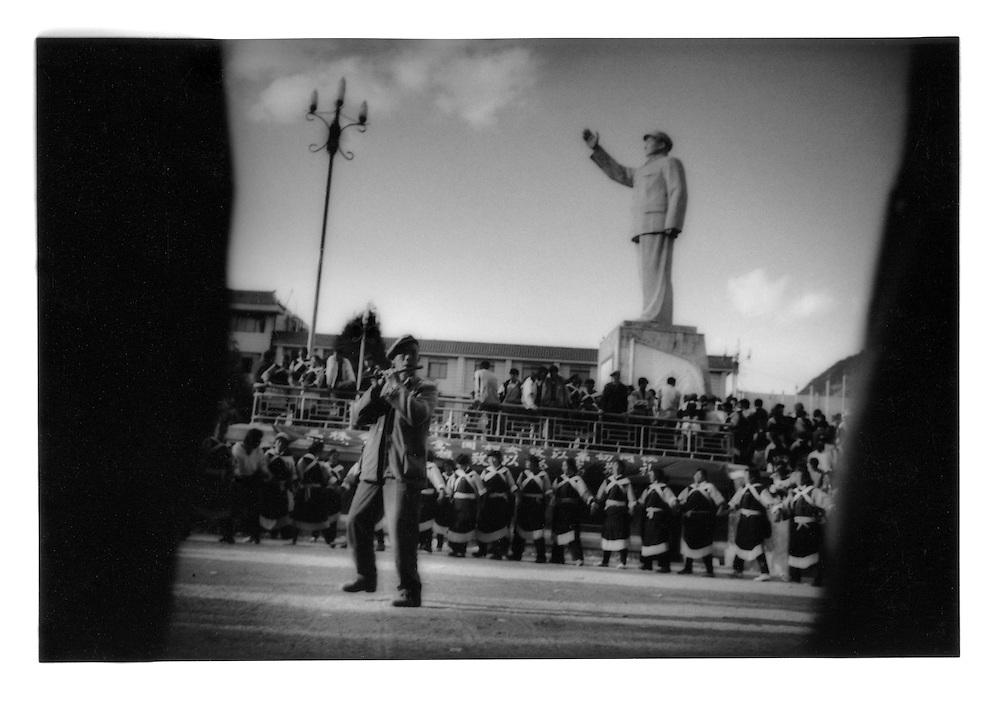 Naxi flutist at a women's festival beneath a statue of Mao.   Lijiang, Yunnan, China.  1997