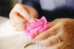 Close up of an Asian woman's hands making a garland for the Baisakhi festival,