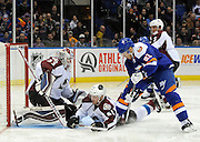 Colorado Avalanche goalie Jean-Sebastien Giguere (35) keeps his eye on a loose puck as Andre Benoit (61) falls to the ice defending against  New York Islanders' Kyle Okposo (21) during an NHL hockey game on Saturday, Feb. 8, 2014, in Uniondale, N.Y. (AP Photo/Kathy Kmonicek)