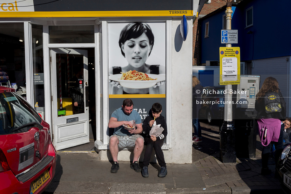 A father and son sit outside a local shop eating chips, on 29th April 2017, at Hastings, East Sussex, England.