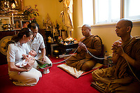 """Catherine Breen Kamkong and Sathaporn Kamkong of their 4 weeks old daughter Sirimaya Claire performing the The Kwan Duan (Kon Pom Fai) Ceremony at the Buddhist Temple in . When a baby is one month old, it is considered to be safe as a """"mankind's child"""". Then the Kwan Duan ceremony is held in order to auspiciously bless the child. If the auspicious occasion is determined to be in the morning, it is customary to invite the monks to perform evening chanting in the day before the auspicious day. This occasion is also a ceremony for laying down the baby into the cradle."""