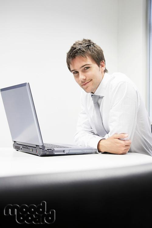 Contented Businessman sitting at desk with Laptop portrait