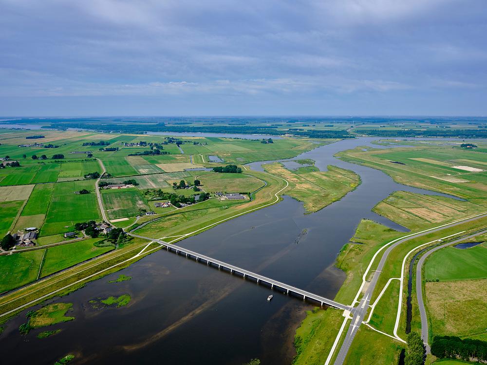 """Nederland, Overijssel, Gemeente Kampen; 21–06-2020; het Reevediep richting monding in het Revemeer (voorheen Drontermeer). In de voorgrond de Nieuwendijkbrug, Flevoland aan de horizon.<br /> Het Reevediep is aangelegd in het kader van het project Ruimte voor de Rivier om bij hoogwater water af te voeren voordat dit het nabij gelegen Kampen bereikt, direct naar het IJsselmeer, de 'bypass Kampen'. Het Reevediepgebied is ook een natuurgebied en vormt een ecologische verbindingszone tussen rivier de IJssel en Drontermeer.<br /> Reevediep towards the mouth in the Revemeer (formerly Drontermeer). In the foreground the Nieuwendijkbrug, Flevoland on the horizon.<br /> The Reevediep has been constructed as part of the Room for the River project, and functions to discharge high waters before reaching the nearby Kampen, directly to the IJsselmeer, the """"bypass Kampen"""". The Reevediep area is also a nature reserve and forms an ecological connecting zone between the river IJssel and Drontermeer.<br /> <br /> luchtfoto (toeslag op standard tarieven);<br /> aerial photo (additional fee required)<br /> copyright © 2020 foto/photo Siebe Swart"""