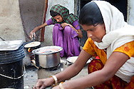 Sadma Khan (in purple), 19, makes lunch in the shared compound of her mother's (in orange) extended family's house in a slum area of Tonk, Rajasthan, India, on 19th June 2012. She was married at 17 years old to Waseem Khan, also underaged at the time of their wedding. The couple have an 18 month old baby and Sadma is now 3 months pregnant with her 2nd child and plans to use contraceptives after this pregnancy. She lives with her mother since Waseem works in another district and she can't take care of her children on her own. Photo by Suzanne Lee for Save The Children UK