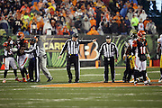 NFL field judge Buddy Horton (82), umpire Mark Pellis (131), and back judge Perry Paganelli (46) try to regain order and clear the field of unnecessary players and coaches after Cincinnati Bengals running back Giovani Bernard (25) gets hit hard by Pittsburgh Steelers inside linebacker Ryan Shazier (50) causing a third quarter fumble, recovered by Shazier, and starting a player melee over no penalty call for unnecessary roughness and leading with the helmet during the NFL AFC Wild Card playoff football game against the Pittsburgh Steelers on Saturday, Jan. 9, 2016 in Cincinnati. The Steelers won the game 18-16. (©Paul Anthony Spinelli)