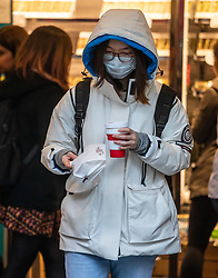 © Licensed to London News Pictures. 05/03/2020. London, UK. A women buys breakfast as she heads to work wearing a mask in Westminster as the Government announces plans to combat the coronavirus disease crisis. Photo credit: Alex Lentati/LNP