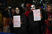 New York, NY - 31 October 2019. the annual Greenwich Village Halloween Parade along Manhattan's 6th Avenue. Two figures in masks with signs asking for Trump's impeachment.