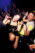 One women with pink glowsticks and novelty contact lenses and and a man with dyed hair, contact lenses, vampire teeth and glowsticks, U.K, 1990s.