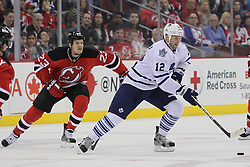 Mar 23; Newark, NJ, USA; Toronto Maple Leafs center Tim Connolly (12) skates with the puck while being defended by New Jersey Devils right wing David Clarkson (23) during the first period at the Prudential Center.