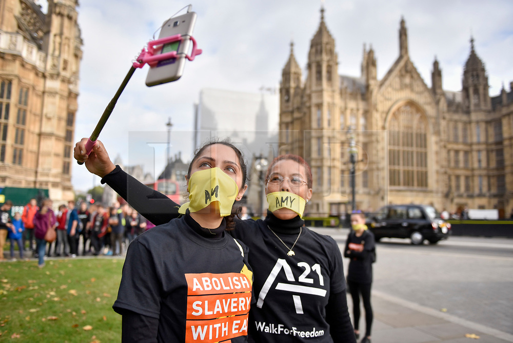 """© Licensed to London News Pictures. 14/10/2107. London, UK. Women prepare to take part in the """"The Walk For Freedom"""", marching around the capital demonstrating against modern slavery.  The protest is co-ordinated with other walks which abolitionist group A21 is staging in 400 cities around the world on the same day. The facemasks represents the silence of modern slaves. Photo credit : Stephen Chung/LNP"""