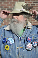 "Merrick, New York, USA. October 23, 2016. FRED S. CHANDLER, 66, of North Bellmore, wearing several political campaign buttons supporting Democratic presidential candidate Hillary Clinton, holds onto his hat in wind while attending rally to demand public water and stop New York American Water (NYAW) rate hike. His hat button was: ""Still love Bernie. Voting for Hillary."" On denim jacket included buttons for Hofstra University DEBATE 2016 - and ""So My Daughter Knows She Can Be President. Hillary 16"" - ""TRUMPBUSTERS"" - ""CLINTON KAINE 16"" - and Monopoly Man character with ""NEVER TRUMP"" text."