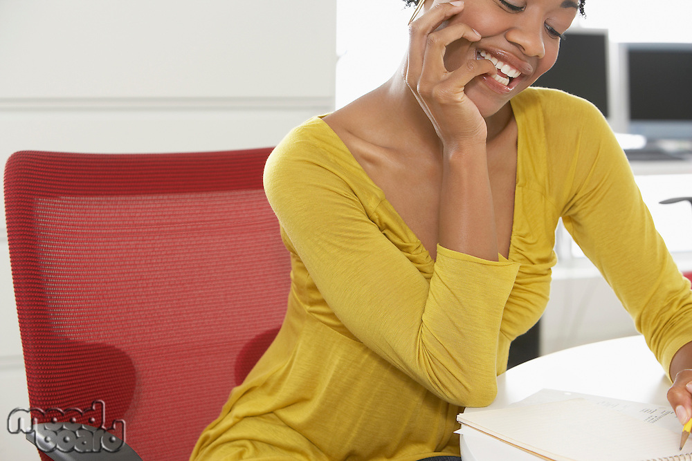 Young woman writing at desk in office