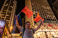 On a night when thousands of Hong Kongers gathered to form a human chain in various parts of the city, a counter-protestor stands at an intersection waving Chinese flags. He would later to be taken away by police to deescalate the situation as protestors taunted and confronted him. <br />
