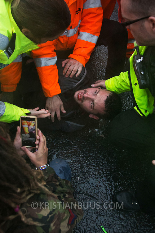 Day two of the Rolling Resistance, Preston New Road, Lancashire. Police attending a bleeding activists. Security violently try to prevent climate protectors to lock-on at the gates to Quadrilla drill site. One activists was restrained by the site manager using pressure points to the neck and throat and pinned to the ground by security staff on the road outside Quadrilla's property. Two activists managed to lock themselves down and block the gates.  A lock-on, where two or more lock themselves together inside a re-inforced tube is used as a peaceful non-violent way of protesting.The New Preston Road Quadrilla site is almost ready to start drilling for shale gas after many delays caused by local objections. Lancashire County council voted against fracking but the conservative central government forced it through.