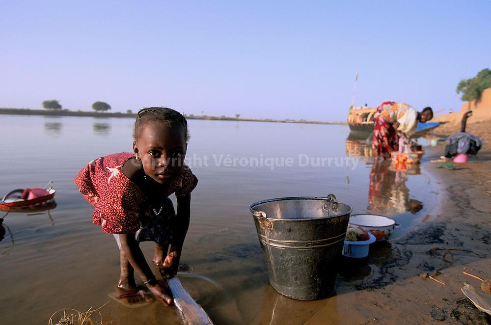 LA CUISINE DANS LE FLEUVE, DIAFARABE, MALI . Cette enfant du village peul de Diafarabe, sur les rives du fleuve Niger, nettoie le poisson de son repas de midi dans les eaux du fleuve. Un peu plus loin, une jeune femme du village fait sa lessive. L'eau du feuve est tout, on s'y lave, on y lave le linge, on y fait la vaisselle, on y peche le poisson Cette enfant du village peul de Diafarabe, sur les rives du fleuve Niger, nettoie le poisson de son repas de midi dans les eaux du fleuve. Un peu plus loin, une jeune femme du village fait sa lessive. L'eau du feuve est tout, on s'y lave, on y lave le linge, on y fait la vaisselle, on y peche le poisson