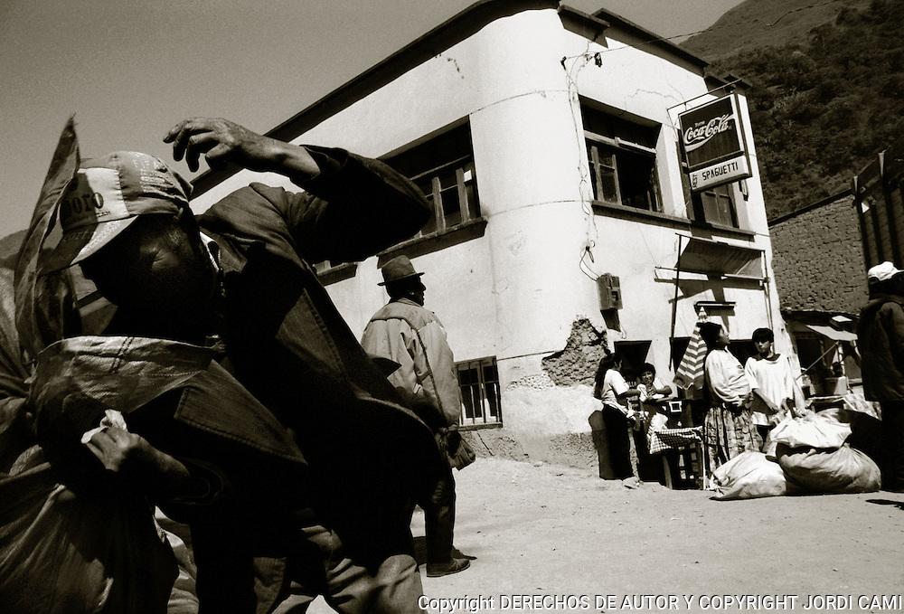 CAMPESINOS ESPERAN CON SUS FARDOS A QUE UN CAMION<br /> ACCEDA A LLEVARLES HASTA SU DESTINO.YOLOSA, LOS YUNGAS.BOLIVIA. FOTO : JORDI CAMI