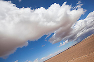 Desert landscape with cloudy blue sky in the Sahara desert of Morocco.