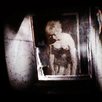 woman in a corset and garters glimpsed through a window