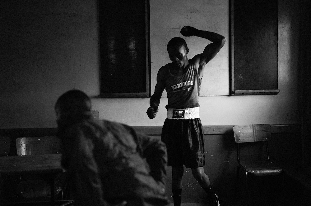 NAIROBI, KENYA - NOVEMBER 17, 2011: Kamau Ng'ang'a (right) prepares for an Olympic Qualifying boxing bout. As a Kikuyu, Ng'ang'a represents the tribe that was targeted most violently during the post-election violence of 2008. Despite his tribal affiliation, Ng'ang'a is the club favorite and hopes to represent the Kibera Olympic Boxing Club in the 2012 Olympics.<br /> <br /> Within Kenya's progressive youth culture is the Kibera Olympic Boxing Club, a group of low-income adolescents from the slum whose leader uses boxing as a way to engage with idle youth. The group's ethnic diversity is remarkable given Kenya's 2008 post-election violence in which people from several tribes were forced violently out of slums. Together, these boxers represent a nascent trend of cross-tribe brotherhood in a healing nation.