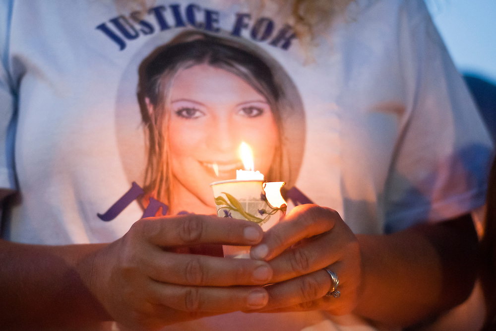 Lathan Goumas for the Midland Daily News..Michelle Berk holds a candle during a vigil for her daughter Jessica Leigh Callan at the Michigan State Police Post in Bridgeport Township, Mich. on Wednesday, July {daY], {yr4}. Approximatley 50 friends and family gathered to remember Callan on the two year anniversary of her murder which has not yet been solved.