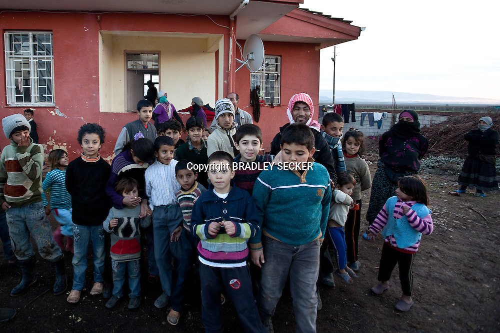 Members of the Jasem family pose for a photo in the garden of their temporary home in Davutpasa village, bordering Syria. The extended family of more than 60 people share three bedrooms and very little food in Davutpasa, Turkey. 12/29/2012. Bradley Secker for the Washington Post