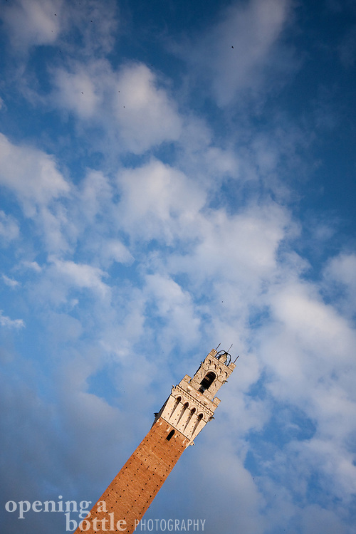 Torre del Mangia on an off-angle, with blue sky and clouds, Siena, Tuscany, Italy.