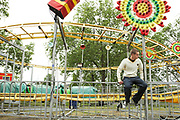 Teenager Sitting On Fairground Ride