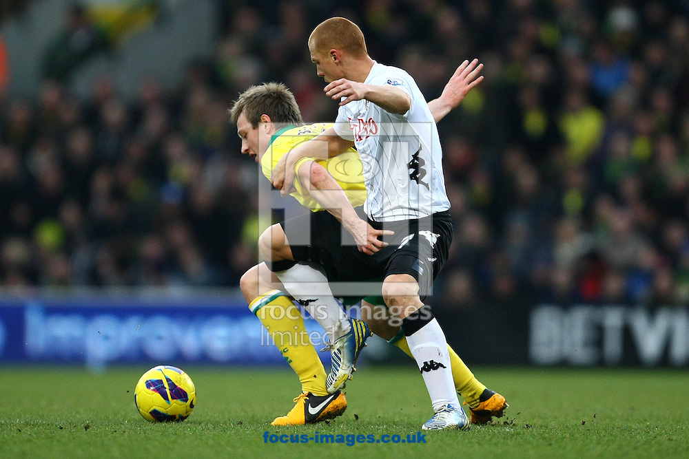 Picture by Paul Chesterton/Focus Images Ltd +44 7904 640267.09/02/2013.Luciano Becchio of Norwich gets to grips with Steve Sidwell of Fulham during the Barclays Premier League match at Carrow Road, Norwich.