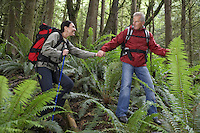 Man and woman walking in forest carrying backpacks holding hands