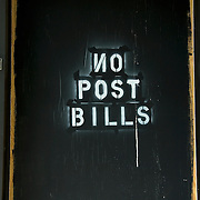 Spray paint sign on wall, No Post Bills such have been Post No Bills. Example of bad grammar and miss , No backwards and miss spelled.