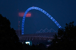 "© Licensed to London News Pictures. 07/05/2020. LONDON, UK.  A full moon, known this month as a Flower moon (named for the arrival of flowers in bloom in May), rises behind the arch of Wembley Stadium (lit up in blue to recognise NHS workers) in north west London.  It is also the last ""supermoon"" to be seen in 2020, where the moon is closest to the earth (the perigee) and appears 6% larger than a normal full moon.  Wembley Stadium is under consideration to be a neutral venue to host Premier League games as part of Project Restart in order for the football season to reach a conclusion after being suspended due to the ongoing coronavirus pandemic.  Photo credit: Stephen Chung/LNP"
