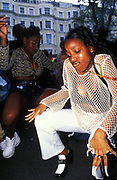 Two girls dancing close to the ground, Notting Hill Carnival, London UK 2000's