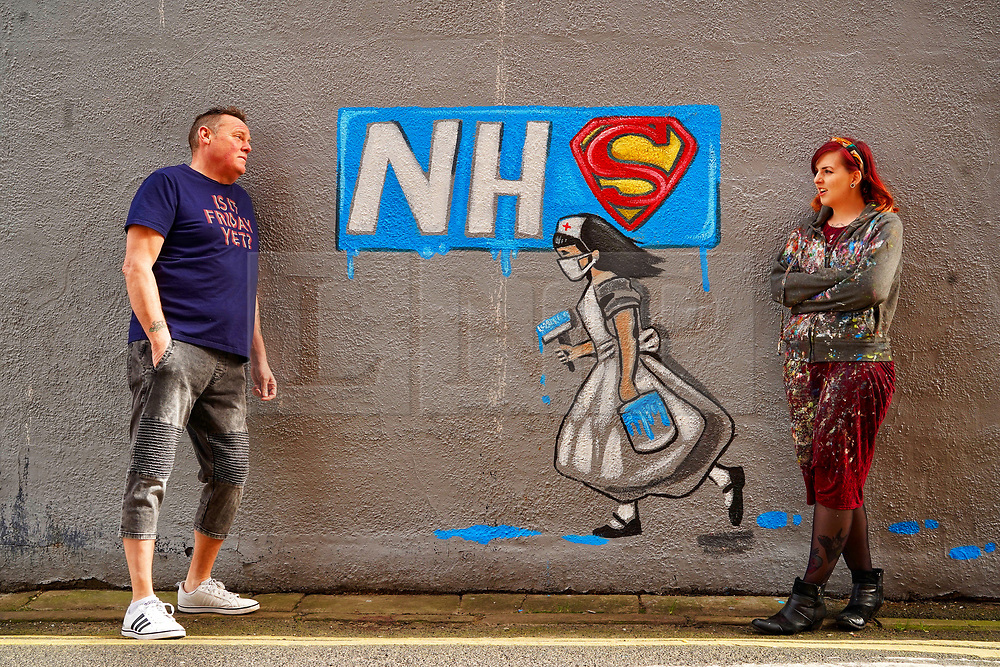 © Licensed to London News Pictures. 03/04/20. Pontefract, UK. Local artist Rachel List (R) chats with landlord Gary Stocks along side a mural she has painted on the wall of the Horse Vaults pub in Pontefract, West Yorkshire in support of the NHS., West Yorkshire. Photo credit: Scott Merrylees/LNP