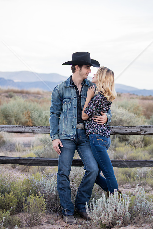cowboy and a girl embracing on a ranch with mountain views