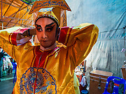 """26 NOVEMBER 2014 - BANGKOK, THAILAND: A Chinese opera performer puts on his costume at the Chow Su Kong Shrine in the Talat Noi neighborhood of Bangkok. Chinese opera was once very popular in Thailand, where it is called """"Ngiew."""" It is usually performed in the Teochew language. Millions of Chinese emigrated to Thailand (then Siam) in the 18th and 19th centuries and brought their culture with them. Recently the popularity of ngiew has faded as people turn to performances of opera on DVD or movies. There are about 30 Chinese opera troupes left in Bangkok and its environs. They are especially busy during Chinese New Year and Chinese holidays when they travel from Chinese temple to Chinese temple performing on stages they put up in streets near the temple, sometimes sleeping on hammocks they sling under their stage.      PHOTO BY JACK KURTZ"""