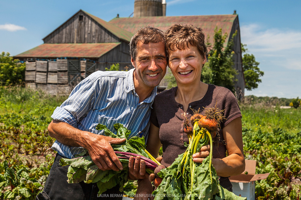 Organic farmers Wolfgang and Regina Pfenning with handfulls of just-harvested golden and red beets on their Ontario farm.