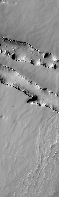 The two depression crossing this image are called Pavonis Fossae and are located just north of the volcano.
