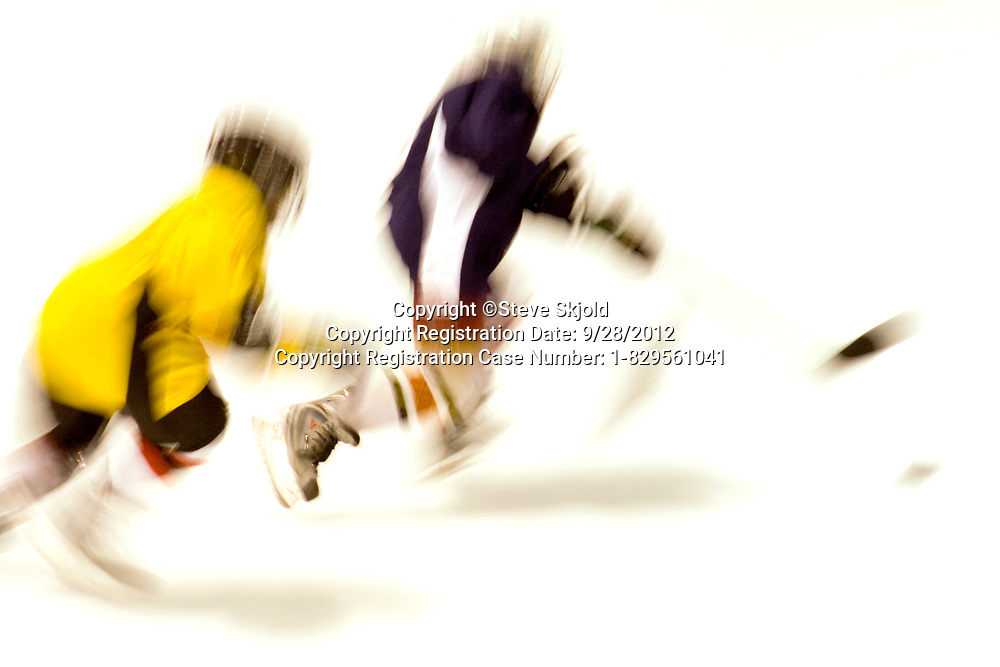 Blurred action of boys age 10 playing hockey. Maplewood Minnesota MN USA