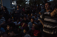 Families wait throughout the night to enter the Moria registration camp on the island of Lesvos, Greece on October 19 2015. Asylum seekers who arrived on Lesvos by sea from Turkey are required to be registered and approved to travel by Greek police before leaving the island. In October and November, over 300,000 thousand asylum seekers were registered at Moria and other hotspots on Lesvos in 2015. Most waited for up to a week, sleeping on the group with limited access to food, water and no bathrooms, in a line that stretched for over a kilometer to be registered at Moria.