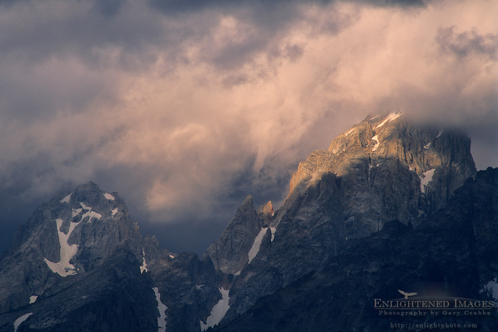Sunlight on storm clouds near the summit of the Grand Tetons, Grand Teton Nat'l. Pk., WYOMING