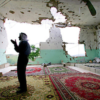 A Lebanese man prays in the remains of a mosque that was heavily damaged during last summer's war with Israel in the village of Siddiqqine in southern Lebanon. July 2007.