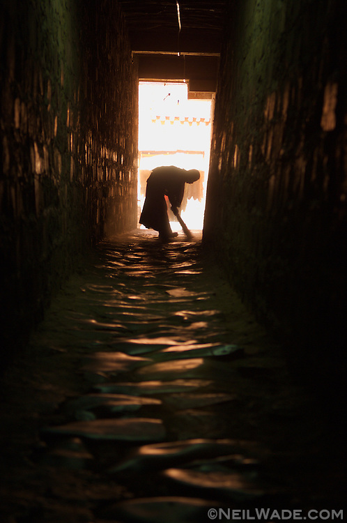 A novice Tibetan Buddhist monk sweeps a dark hallway in a monastery in Shigatse, Tibet (China).