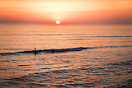 Last surfer, riding last wave at last light during sunset at Terramar Beach in Carlsbad, CA.