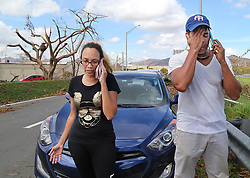 Carlos Rolâ¤â€n, a financial planner and his wife Nerys Medina, from the town of San Lorenzo, stop along the Caguas road to call their relatives in Orlando Florida to communicate to them their decision to leave Puerto Rico October 2. It is a decision against their will since their house got damaged, he is jobless and their daughters' schools are closed for an unknown amount of time forcing many Puerto Ricans to fly to the U.S. after Hurricane Maria, (category 4) passed through Puerto Rico devastating the island leaving residents without power and ways to communicate on Sept. 20. on October 02, 2017. Photo by Pedro Portal/Miami Herald/TNS/ABACAPRESS.COM