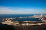 Nederland, Rotterdam, Maasvlakte, 20-03-2009; De Slufter, grootschalige opslagplaats voor vervuild havenslib. De verontreinigde baggerspecie komt voort uit het onderhoudsbaggerwerk in de Rotterdamse haven waarbij de haven op diepte wordt gehouden. Langs de rand van de Slufter zijn windmolens gebouwd en in de Noordzee, direkt achter het depot, wordt de Tweede Maasvlakte aangelegd. Rechts riching horizon de poederkoolgestookte elektricitieitscentrale van E.ON (EON).  The Slufter area in the South-West of the Netherlands, large-scale depot of contaminated harbor sludge from the Port of Rotterdam. Along the edge of the Slufter windmills are built in the North Sea, immediately behind the depot, the Second Maasvlakte will be constructed. Swart collectie, luchtfoto (toeslag); Swart Collection, aerial photo (additional fee required); .foto Siebe Swart / photo Siebe Swart