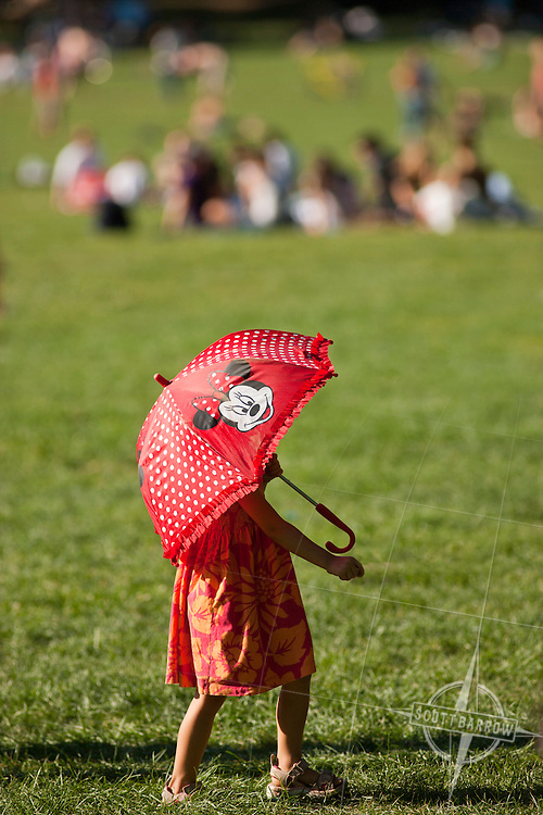 Young girl with a Minnie Mouse umbrella on a summer day on Sheeps Meadow, Central Park, NYC.